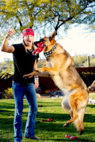 Michaels tosses a Pets Rock toy for one of his German Shepherds.